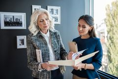 Serious stylish aged female is standing with her employee Royalty Free Stock Photos