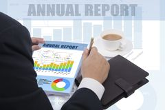 Annual report reviewed by businessman. Chairman reviewed company annual report with infographic on background Stock Photo