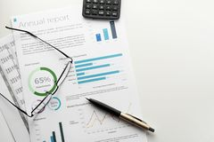 Annual report sheet with charts, pen, calculator and eyeglasses on white desk. Mockup annual report sheet with charts and graphs, pen, calculator and eyeglasses stock images