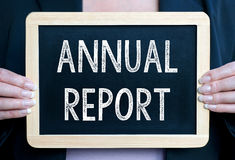 Annual report. Woman holding wood framed chalkboard with annual report written in white chalk Royalty Free Stock Image