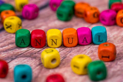 Annual - word created with colored wooden cubes Royalty Free Stock Images