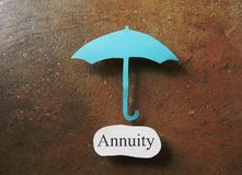 Annuity Investment. Paper umbrella over an Annuity message Stock Image
