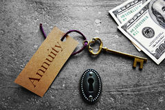 Annuity key. Gold key with Annuity tag, with keyhole and cash Royalty Free Stock Photo