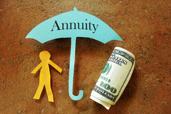 Annuity umbrella. Over a paper cutout person and hundred dollar bill Royalty Free Stock Photo