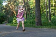 Annulé trois années de fille de coureur sur le sentier piéton de parc d'asphalte tenant le morceau de craie de trottoir photographie stock