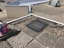 Annulation d'un conduit ; Réparations de toit sur le toit d'EPDM lesté par message publicitaire ; Toit plat images libres de droits