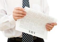 Annunci della lettura dell'uomo d'affari da documento immagini stock