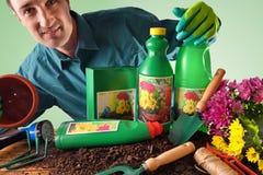 Annuncio pubblicitario che mostra le bottiglie ed i contenitori dei prodotti di giardinaggio Immagine Stock
