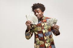 Annusata nel piacere Occhi chiusi dell'uomo africano, tenenti i suoi soldi Immagini Stock