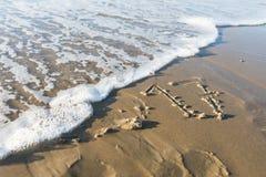 Ano 2017 escrito na areia da praia e apagado pelo wav Fotos de Stock Royalty Free