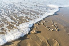 Ano 2017 escrito na areia da praia e apagado pelo wav Fotografia de Stock