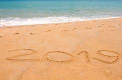 Ano escrito 2019 na praia da areia no mar fotos de stock royalty free