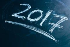Ano número 2017 escrito com o giz branco no quadro-negro Fotografia de Stock