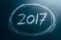 Ano número 2017 escrito com o giz branco no quadro-negro Foto de Stock