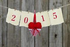Ano 2015 na suspensão de papel antiga de pergaminho na corda com coração vermelho pelo fundo de madeira Imagens de Stock