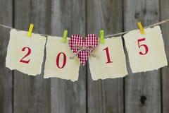 Ano 2015 no papel antigo com o coração vermelho que pendura na corda pela cerca de madeira gasto Fotografia de Stock