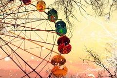 Ano novo 2018 Dois mil dezoito Ferris Wheel Árvores despidas sob uma queda de neve contra o céu do nascer do sol Sonho do inverno Foto de Stock Royalty Free