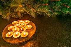 Ano novo e Natal, pinho artificial verde em um fundo preto à vista das velas da cera Toques caseiros mornos amarelos, mim imagens de stock