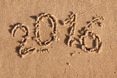 Ano novo 2016 escrito na areia no sol da manhã Fotos de Stock Royalty Free