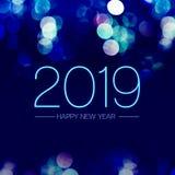 Ano novo feliz 2019 com a efervescência azul da luz do bokeh na obscuridade - fundo roxo azul, cartão do feriado fotografia de stock royalty free