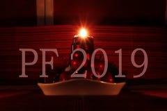 Ano novo feliz 2019 com o castiçal caseiro do Natal Uma de quatro velas que queimam e que mostram raios bonitos Desejo a você fotos de stock