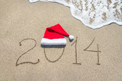 Ano novo feliz 2014 com o chapéu de Santa na areia da praia do mar com onda Foto de Stock