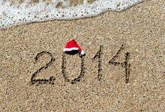 Ano novo feliz 2014 com o chapéu do Natal no Sandy Beach - feriado Foto de Stock