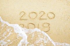 Ano novo feliz 2020 e 2019 escritos na areia aonde 2019 est?o obtendo lavado afastado pela onda fotos de stock