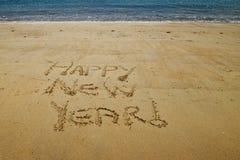 Ano novo feliz escrito na areia dourada de pouca praia de Kaiteriteri foto de stock royalty free