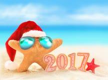 Ano novo feliz Estrela do mar no chapéu de Santa na praia do verão Fotografia de Stock