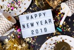 Ano novo feliz 2019 na caixa leve com copo do partido, ventilador do partido, lata imagens de stock royalty free