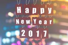 Ano novo feliz 2017 a palavra do alfabeto em etiquetas de papel vermelhas no bokeh ilumina-se Fotos de Stock Royalty Free