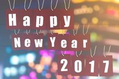 Ano novo feliz 2017 a palavra do alfabeto em etiquetas de papel vermelhas no bokeh ilumina-se Imagens de Stock