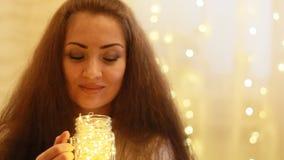 Ano novo Natal Realizar bonitos da mulher nas mãos uma lâmpada, fecham seus olhos e sonho no fundo das luzes filme