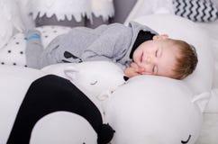 Ano novo no estilo escandinavo, árvore de Natal, mamã com uma criança, brinquedos do ` s das crianças, bebê do sono Fotos de Stock Royalty Free