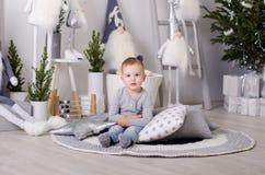 Ano novo no estilo escandinavo, árvore de Natal, mamã com uma criança, brinquedos do ` s das crianças, bebê do sono Fotos de Stock