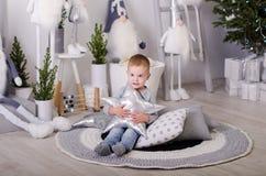Ano novo no estilo escandinavo, árvore de Natal, mamã com uma criança, brinquedos do ` s das crianças, bebê do sono Imagem de Stock