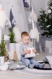 Ano novo no estilo escandinavo, árvore de Natal, mamã com uma criança, brinquedos do ` s das crianças, bebê do sono Imagens de Stock
