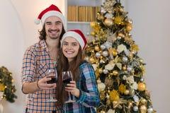 Ano novo próximo decorado feliz Santa Hat do desgaste da árvore do ano novo do suporte dos vidros de vinho da posse dos pares do  Imagens de Stock Royalty Free