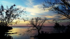 Anoitecer no lago com céus azuis e árvores fotografia de stock royalty free