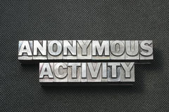Anon activity bm. Anonymous activity phrase made from metallic letterpress blocks on black perforated surface royalty free stock photos