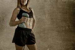 Anoniem geschikt en sterk de holdingsgewicht van de sportvrouw bij haar hand stellen uitdagend in koele houding Stock Foto
