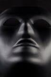 Anoniem zwart masker die van pikzwarte achtergrond uitpuilen - hij royalty-vrije stock foto