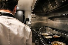 Anonieme chef-kok die zich op restaurantkeuken bevinden stock foto's