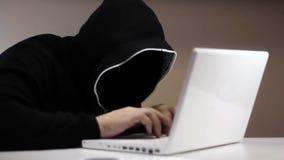 Anonieme hakker in zwarte kap met laptop stock footage