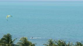 Anonieme kiteboarder in kalme overzees Verre persoon met vlieger berijdende raad op kalme oppervlakte van blauw zeewater op tropi stock footage