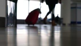 Anonieme mensen die door een luchthaventerminal lopen met koffers, zakken en bagage stock video