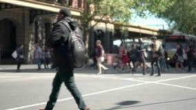 Anonieme mensen die een kruising met tram op achtergrond kruisen stock video