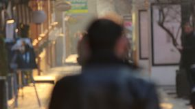 Anonieme mensen die op de gouden zonsondergang als achtergrond in de stad lopen Defocusedvideo stock footage