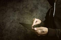 Anonieme niet identificeerbare mannelijke persoon die met een kap tabletcomputer met behulp van Stock Foto's